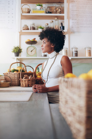 side bar: Side portrait of young woman employee standing at juice bar counter. African female fruit juice bar owner. Stock Photo