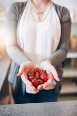cropped shot: Cropped shot of a womans hands holding strawberries. Female holding a handful of fresh strawberries.