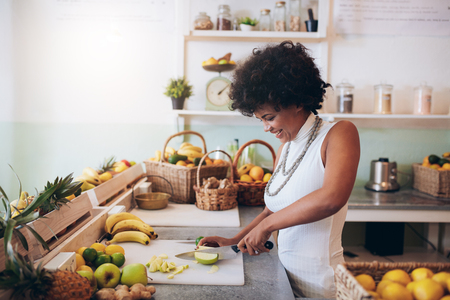 juice bar: Shot of young african woman working at juice bar and cutting fruits. Female bartender making fresh juice. Stock Photo