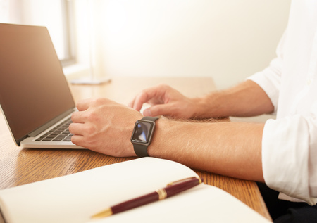 businessman working at his computer: Close up image of businessman working on laptop. Man  with a smartwatch using laptop computer while sitting at his desk.