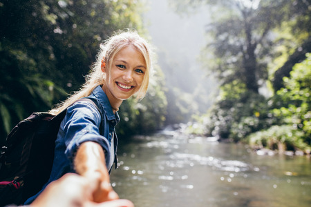 Portrait of happy young woman holding hand of her boyfriend while walking by mountain stream. Couple enjoying a hike in nature.