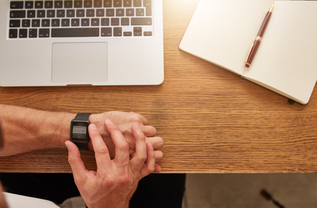time table: Top view shot of man sitting at his workplace checking time on his smartwatch. Businessman looking at his watch. Focus on smart wrist watch in mans hand.