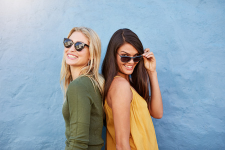 casuals: Portrait of happy young female friends standing together against blue background. Both in stylish casuals and sunglasses.