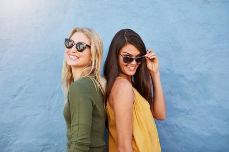 Retrato de feliz jóvenes amigos femeninos de pie juntos contra el fondo azul. Ambos en casuals elegantes y gafas de sol.