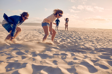 Two young friends competing in a race on a sandy beach. Young man and woman running a race on the beach. photo