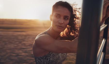 Close up Portrait der entschlossenen jungen Frau am Strand und auf der Suche in den Abend entfernt. Fitness Frau am Übungsplatz bei Sonnenuntergang am Strand trainieren. Standard-Bild - 60027402