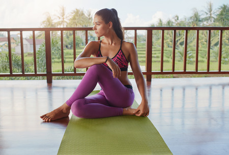 Shot of young caucasian woman sitting on yoga mat and looking away. Fitness female relaxing after workout session. Stockfoto