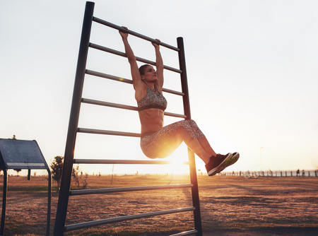 Portrait of strong young woman hanging on wall bars with her legs up. Fitness woman performing hanging leg raises on outdoor.