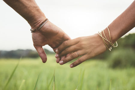 Horizontal shot of young couple walking through meadow holding hands with focus on hands .