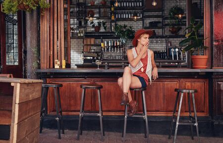 bar stool: Young woman with hat smoking in a bar. Holding cigarette and looking away.