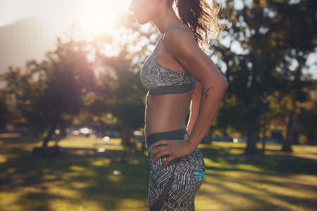 sixpack: Cropped shot of strong young woman standing with her hands on hips. Strong woman with sixpack abdominals. Fit female athlete in sportswear standing at a park.