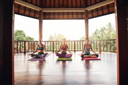 center position: Three women practicing yoga in class. Fitness people sitting in lotus position and meditating at health center.