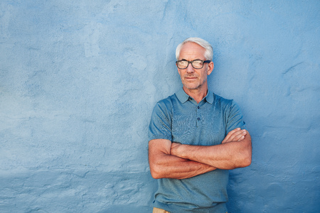Portrait of a handsome mature man wearing glasses standing against blue background. Man with arms crossed looking away at copy space against blue wall. Stock Photo