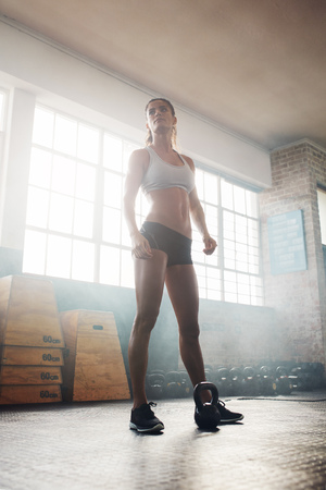 tough woman: Full length shot of muscular woman standing in crossfit gym and looking away. Tough fitness female model with kettle bell on floor. Stock Photo