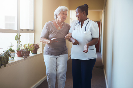 Portrait of happy healthcare worker walking and talking with senior woman. Elder woman gets help from nurse for a walk through nursing home.
