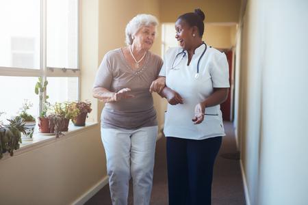 mujer trabajadora: Retrato de feliz trabajador de la salud, caminar y hablar con la mujer mayor. vieja mujer que recibe ayuda de la enfermera a dar un paseo a través de hogar de ancianos.