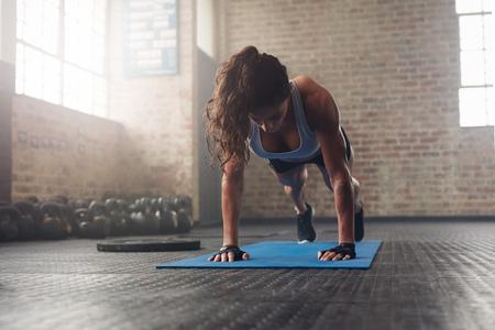 Jonge gespierde vrouw die kern oefening op fitness mat in de sportschool. Fit vrouwelijke ligsteunen doen tijdens de training in de health club. Stockfoto
