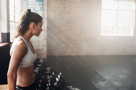 adult woman: Shot of a fit young woman in sportswear at the gym with copy space. Side view of muscular female athlete relaxing after workout. Stock Photo