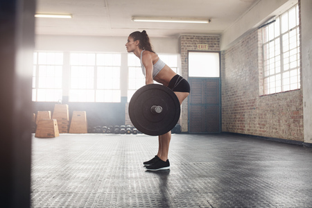 Muscular woman in a gym doing heavy weight exercises. Young woman doing weight lifting at health club. Stock Photo