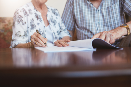 Close up shot of senior woman signing documents with her husband. Elderly caucasian man and woman sitting at home and signing some paperwork, focus on hands. Stock Photo