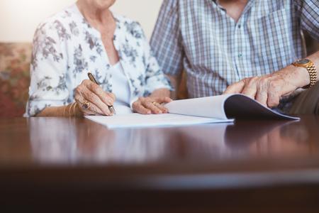 Close-up shot van senior vrouw ondertekend documenten met haar man. Oudere Kaukasische man en vrouw zitten thuis en ondertekenen wat papierwerk, focus op handen.