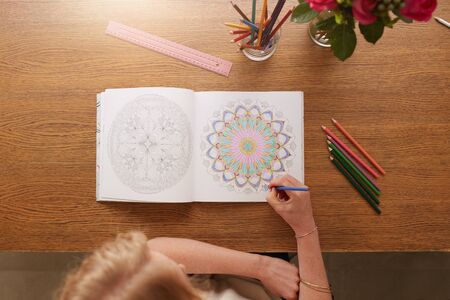 overhead: Overhead view of woman drawing in adult colouring book at home. Stock Photo