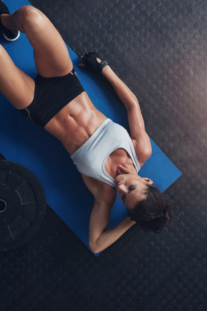 laying abs exercise: Top view of fitness woman relaxing after exercise session on floor. Young female lying on exercise mat in gym. Stock Photo
