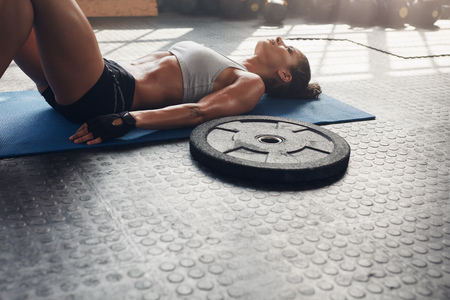 heavy weight: Shot of fitness woman lying on exercise mat with a heavy weight plate on floor. Muscular female relaxing after heavy weight workout.