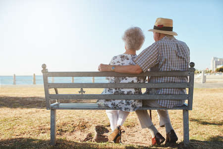 looking out: Rear view of elderly couple relaxing on a bench looking out to sea. Senior man and woman sitting on a bench outdoors and enjoying the view.