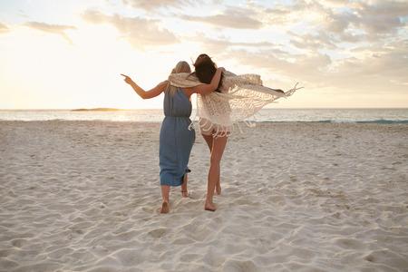 Pełna długość lusterka Shot dwie kobiety przyjaciółmi idzie razem na plaży. Koleżanki na spacer na brzegu morza i zabawy.