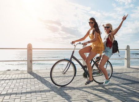 Joyful young women riding a bicycle together. Best friends having fun on a bike at the seaside promenade. Stock Photo