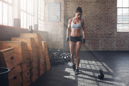 Full length shot of young woman in sportswear taking a walk in the cross fit gym and looking at kettle bell on floor. Fitness female getting ready for intense crossfit workout.