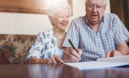 person writing: Portrait of a senior couple signing documents. Senior caucasian man and woman sitting on sofa and signing some paperwork, focus on hands. Stock Photo