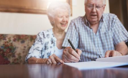 persona escribiendo: Retrato de un hombre de documentos firma de los pares. Senior hombre caucásico y la mujer sentada en el sofá y firmar unos papeles, se centran en las manos.