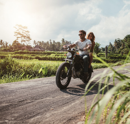 Outdoor shot of couple on motorbike driving through country road. Man and woman riding motorcycle on a countryside road. Stock Photo