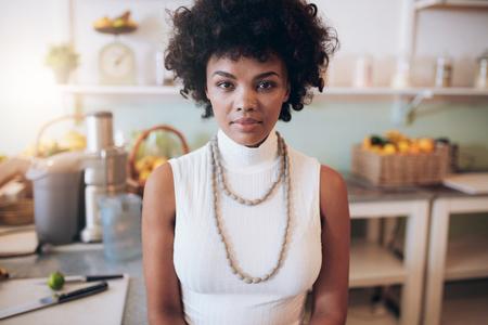 Közeli portré fiatal afrikai nő állt juice bárban. Vonzó női nézi kamera.
