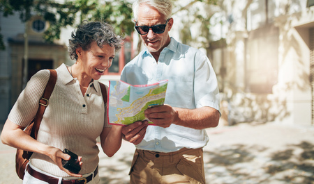 Senior couple of on vacation reading the tourist map. Mature man and woman looking at a map while exploring a city.