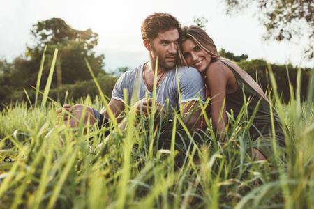 Schot van aanhankelijk jonge paar genieten van een dag in de buitenlucht. Man en vrouw zitten op het gras veld op een zomerse dag.