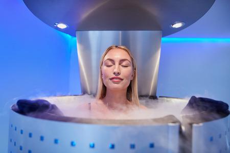 Portrait eines glücklichen jungen Frau in einem ganzen Körper Kryotherapie Kabine mit ihren Augen geschlossen. Kryosauna Kammer für die allgemeine Steigerung der Muskelleistung. Standard-Bild