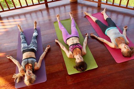 Savasana ポーズ ヨガのスタジオでの人々 のグループの俯瞰。トレーニングの後のヨガマットの上に横たわる若い女性。死体のポーズで床にリラックス