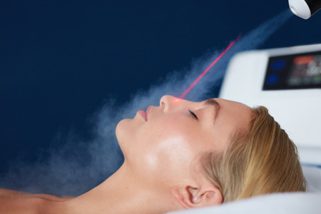 resurfacing: Localized cryotherapy session on the face of young woman. Treatment uses vaporized nitrogen to lower the skin temperature. Stock Photo