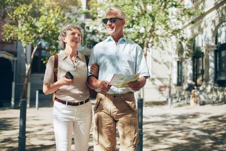 roaming: Middle aged couple roaming around the city holding a map. Senior couple with a map walking in the town.