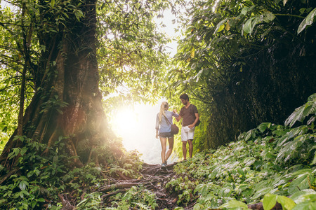 travel woman: Young man and woman hiking in tropical jungle. Couple of hikers walking along forest trail. Stock Photo