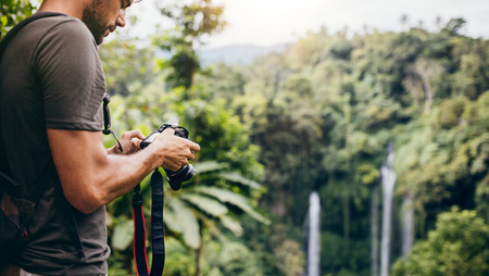one young man: Young man looking at his camera while standing by a waterfall in forest. Male hiker standing on a cliff and looking the waterfall pictures in his digital camera. Stock Photo