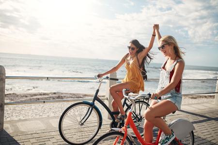 女性朋友們享受著騎自行車在一個夏天的一天。兩位年輕的女性朋友騎在海濱長廊他們的自行車。