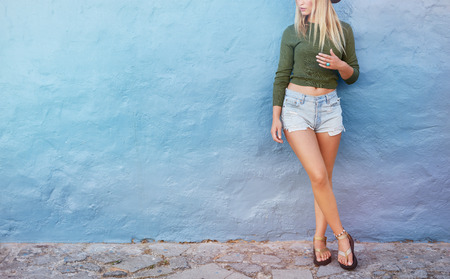 Cropped shot of stylish female model standing against blue wall. Young caucasian woman with copy space.