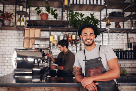 Portrait of male coffee shop owner standing at the counter with barista working in background making drinks.