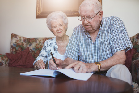 Indoor shot of elderly couple at home signing paperwork together. Retired man and woman sitting on couch and going through some retirement paperwork.