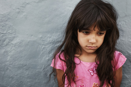 Cerca retrato de niña infeliz de pie contra la pared gris con copia espacio. La chica joven que parece trastornado. Foto de archivo