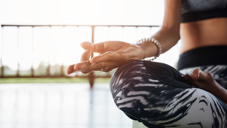 hand position: Close up of woman hand in yoga pose. Healthy female meditating in the lotus position at the gym. Stock Photo